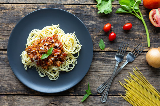 Spaghetti on black plate on wooden background. top view