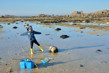 Un petit garçon qui pêche à pieds l'hiver en Bretagne