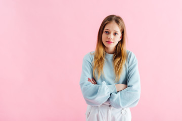 offended teenage girl with crossed arms isolated on pink