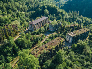 Ruined lost overgrown mining ghost town Akarmara, consequences of war in Abkhazia, aerial view from drone Wall mural