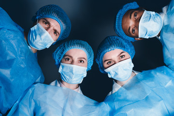 Doctors In Operation Theater Looking At Patient