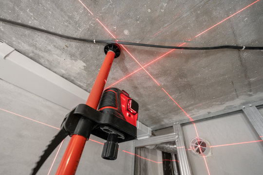 Laser measurement during renovation. Construction tools and equipment. Red laser light lines for level measure.