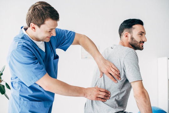 chiropractor massaging back of good-looking man in hospital