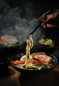 Hand with chopsticks takes noodles of ramen soup. Traditional Asian cuisine