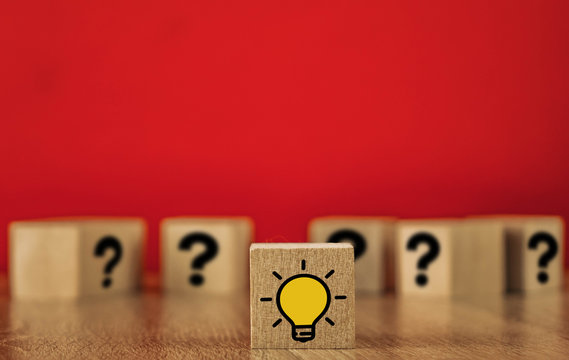 wooden cube with marks and light bulb. light bulb denotes an idea. on red background.