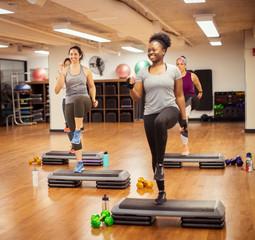 Smiling female athletes exercising on aerobic steps in gym