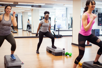 Smiling female athletes exercising on aerobics steps against mirror in gym