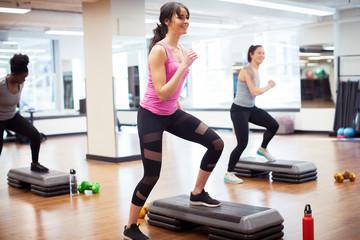 Smiling confident female athletes exercising on aerobics steps in gym