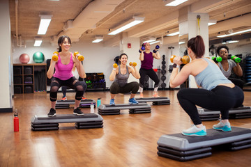 Female trainer and athletes exercising with dumbbells on aerobic steps in gym
