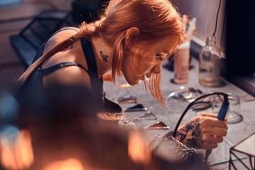 Fototapeta Beautiful diligent woman is doing soldering at her own artisan lamp studio. obraz