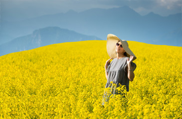 Smiling pretty girl  in blooming yellow field with mountains on background.
