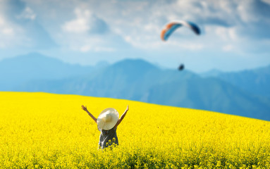 Smiling pretty girl in blooming yellow field with hands up. Looking at the kite in the sky.