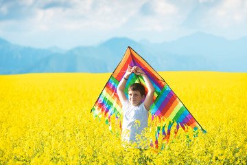 Little boy in white shirt running with kite in the booming yellow field on summer day.
