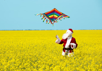 Christmas Santa Claus fling a kite in blooming yellow field. Spring vacation concept.