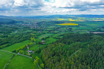 Foto op Plexiglas Groene Aerial perspective view on sudety mountains with touristic city in the valley surrounded by meadows, forest and rapeseed fields