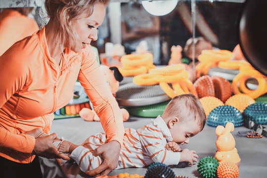 Young happy mom is plaing with her newborn baby at masseur cabinet full of special treatment toys.