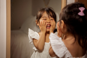 Smiling little girl looking in mirror at home