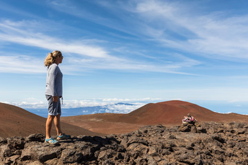 USA, Hawaii, Mauna Kea volcano, female tourist looking at view over volcanic landscape