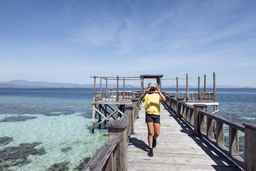 Indonesia, Komodo National Park, girl on a jetty taking a picture