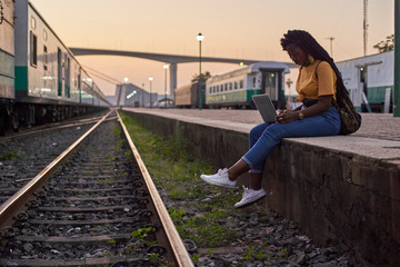 Young woman sitting on platform at the train station using laptop
