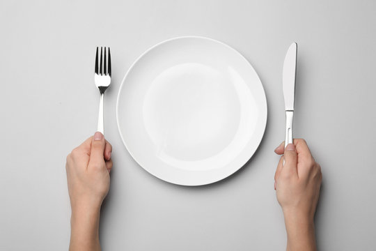 Woman with fork, knife and empty plate on grey background, top view