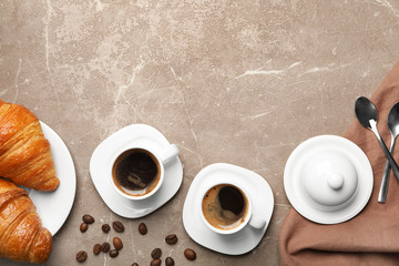 Flat lay composition with cups of coffee and croissants on grey background. Space for text