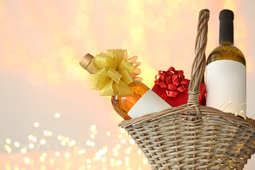 Wicker basket with bottles of wine and gift box against blurred lights. Space for text