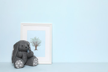Soft rabbit and picture on white background, space for text. Child room interior decor