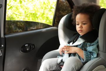 Cute African-American girl sitting in safety seat alone inside car. Child in danger