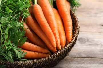 Basket of carrots on wooden background, closeup