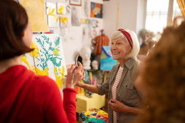 Cheerful retired woman teaching her students to paint