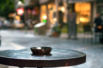 A bar round wooden table with an ashtray, outdoors in the evening, copy space.