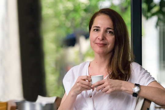 Portrait of a woman, 48 years, having a cup of espresso coffee sitting outdoors.