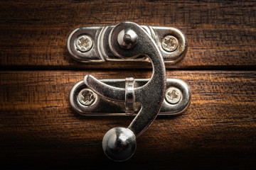 An elegant metal sliding clasp lock screwed into the lid of a wooden box.