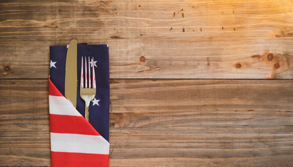 Fourth of July Table Place Setting with silverware and flag napkin on rustic wood background with room or space for copy, text, or your words.  It's an extra wide horizontal with warm light leaks. Wall mural