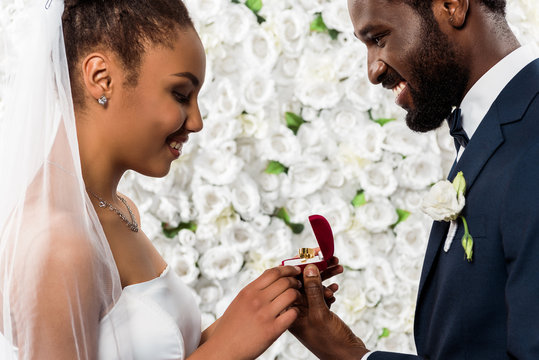 cheerful african american bride looking at box with ring near happy bridegroom and flowers
