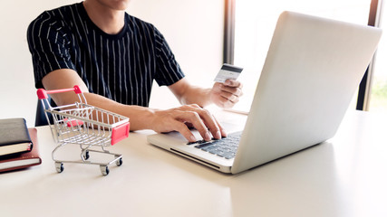 Man holding credit card in hand and entering security code using smart phone on laptop keyboard, online payment shopping concept