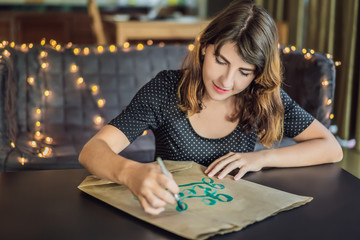 Go green. Calligrapher Young Woman writes phrase on white paper. Inscribing ornamental decorated letters. Calligraphy, graphic design, lettering, handwriting, creation concept