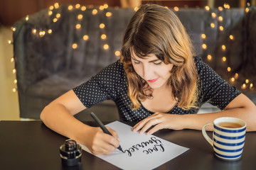 Love yourself. Calligrapher Young Woman writes phrase on white paper. Inscribing ornamental decorated letters. Calligraphy, graphic design, lettering, handwriting, creation concept