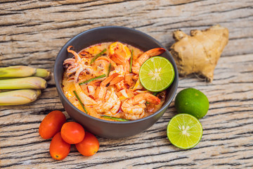 Prawn and lemon grass soup with mushrooms,Tom Yam Kung ,thai food in wooden background, top view