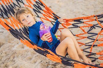 happy little boy relaxed in hammock on sand beach
