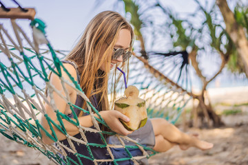 Young woman on the beach in a hammock with a drink