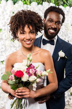 cheerful african american bride holding bouquet with flowers near bridegroom