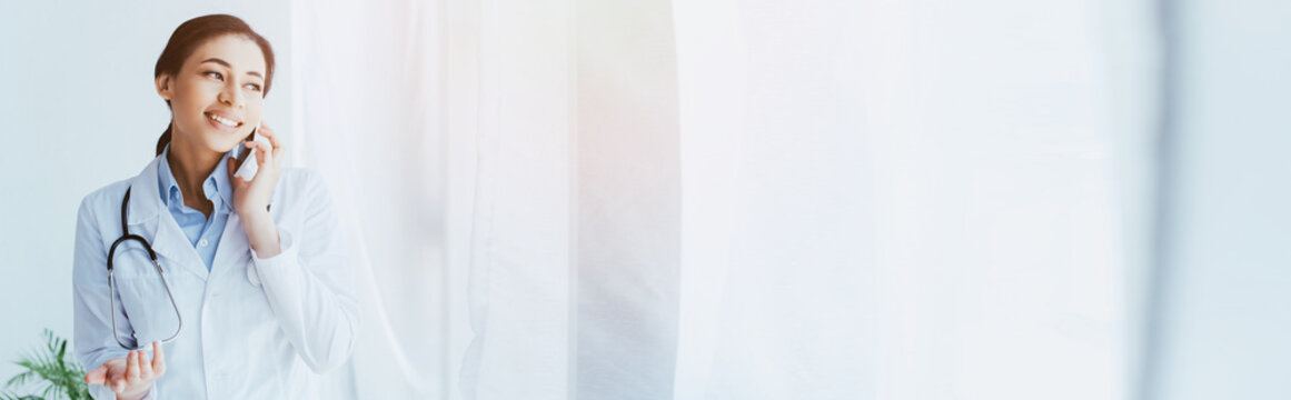 panoramic shot of smiling latin doctor talking by smartphone and looking away