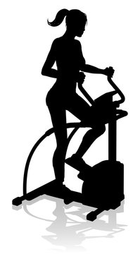 A woman in silhouette using an elliptical cross fit gym equipment exercise machine