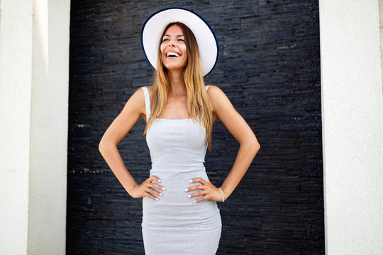 Portrait of sexy cheerful woman wearing white dress and straw hat in sunny day