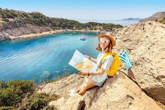 Girl tourist student with map and greek flag standing on top of the hill at background of the inspirational blue lagoon bay. Solo Travel in Greece concept