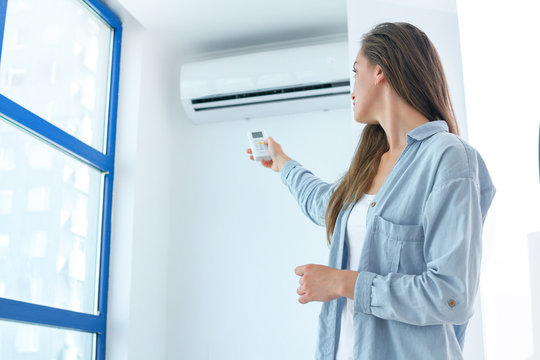 Young attractive woman using remote controller for adjustment air conditioner temperature in room at home.