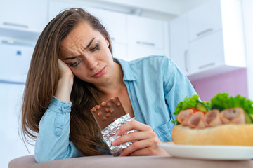 Sad, unhappy stressed crying woman eating chocolate and sweets because of depression and emotional stress. Nerve food. Life problems and difficulties. Food addiction