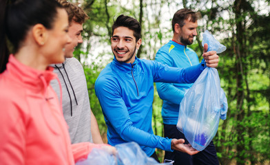 Group of fit people picking up litter in nature, a plogging concept.